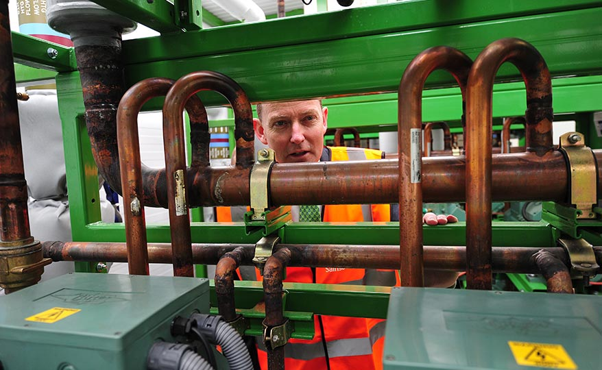 A man looking at industrial pipes, highlighting Sainsbury's commitment to operational carbon