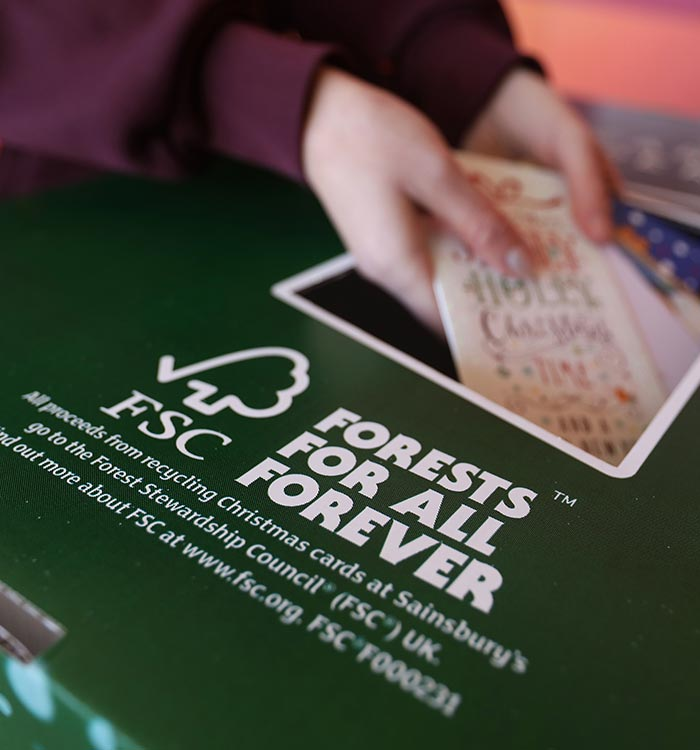 A Sainsbury's colleague putting Christmas cards into a green recycling box to support the FSC